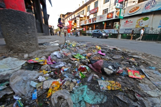 Trash Day Curbside Pile in Kathmandu, Flattened by Rush-Hour Traffic