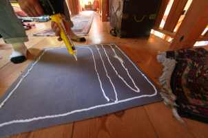 Silicone caulking works perfectly on the backside of your carpet pad for making a tacky-impermanent sticking surface for adhering your pad to a wooden floor.