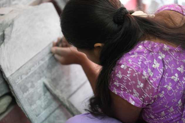 A Young Nepali Artist Carving Prayers Onto a Mani Stone. Photo © Liesl Clark