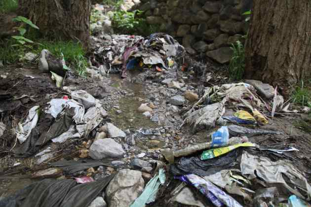 A dried riverbed of trash found outside the beautiful village of Ghami while the water was diverted for a few hours. This garbage waterfall is about 1/4 mile long. © Liesl Clark